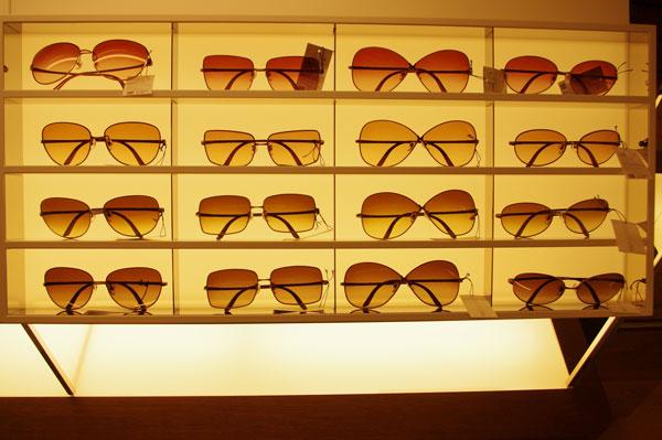 spectre JINS(スペクトル ジンズ)六本木ヒルズ店。間接照明と JINS(ジンズ)オリジナル什器を生かした店内は、サングラスのひとつひとつが見やすく並べられている。