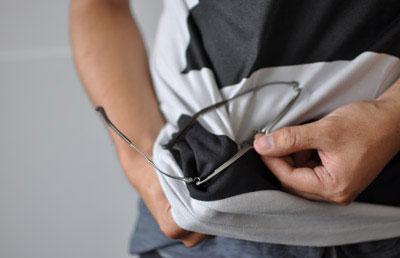 (写真3)wipe T shirt の bottom でメガネを拭いている様子。