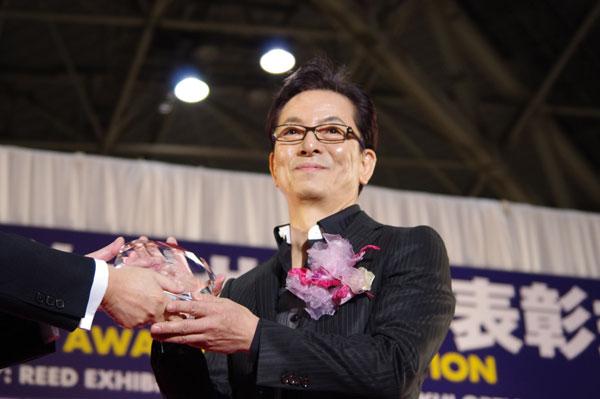 トロフィーを受け取り笑顔を浮かべる水谷 豊氏。 image by GLAFAS