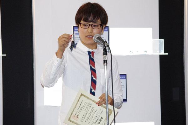 グランプリ受賞製品と表彰状を手にスピーチするボストンクラブのデザイナー青山博美氏。