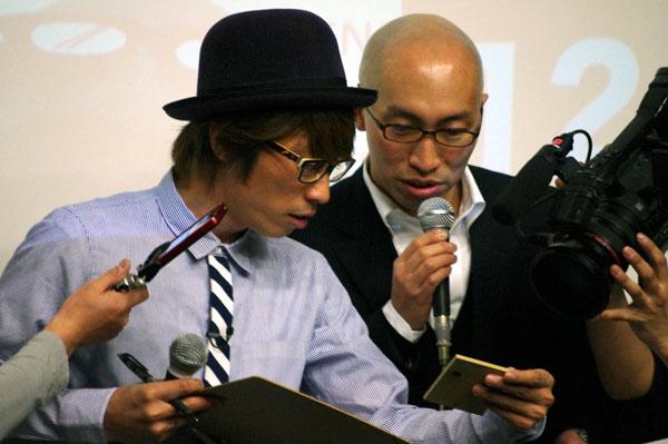 (写真1)会場に来ていた応募者が持参したCMに使った素材を手にコメントする田村淳さん(左)と、JINS(ジンズ)の矢村功氏(クリックして拡大)。image by GLAFAS