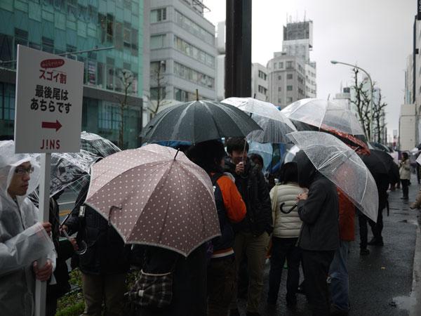 (写真1)雨が降る中、割引クーポンを求めて行列をなす人々。image by JINS