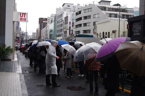 (写真2)雨が降る中、割引クーポンを求めて行列をなす人々。image by JINS