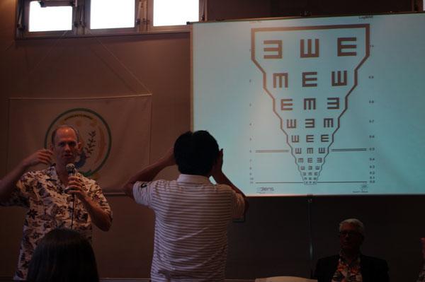 (写真12)adlens P.O.V.(アドレンズ ピーオーヴィー)の使い方をレクチャーするアドレンズ社のグラム・マッケンジー氏(写真左)と、実際に自分で度数を調節できるメガネを体験した参加者(写真・中央)。