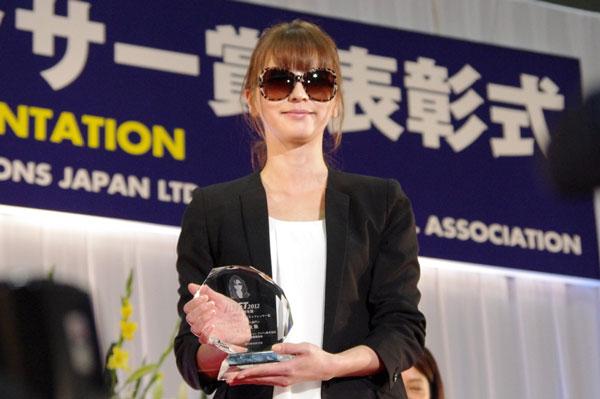 (写真2)第25回「日本 メガネ ベストドレッサー賞」サングラス部門のトロフィーを手にする香里奈さん。トロフィーには、香里奈さんの顔が彫られている。image by GLAFAS【クリックして拡大】