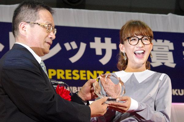 (写真1)第25回「日本 メガネ ベストドレッサー賞」芸能界部門を受賞し、笑顔でトロフィーを手にする優木まおみさん。image by GLAFAS【クリックして拡大】