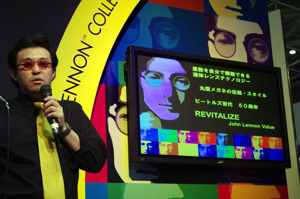 自ら「JOHN LENNON(ジョン・レノン)」のサングラスを掛けてスピーチする、アドレンズ・ジャパンの中島義展社長。image by GLAFAS【クリックして拡大】