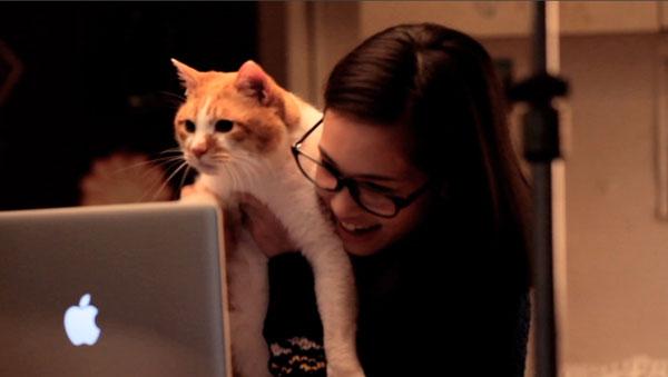 ネコを抱いてパソコンの画面を見つめる水原希子さん。【クリックして拡大】