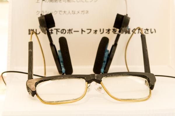 ヘッドホンをつけたときに耳が痛くならないよう、テンプル(つる)先端部には細いワイヤーを採用。 さらに、テンプル(つる)を上下に開く構造にすることで、メガネをヘッドホンに掛けることができるのもポイント。 【クリックして拡大】