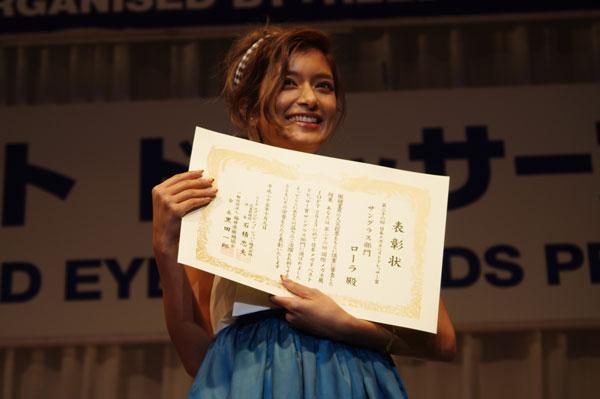 表彰状を手に笑顔のローラ。 【クリックして拡大】