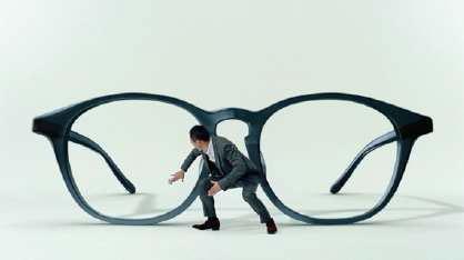 巨大なメガネレンズを拭く渡辺謙。 image by メガネトップ