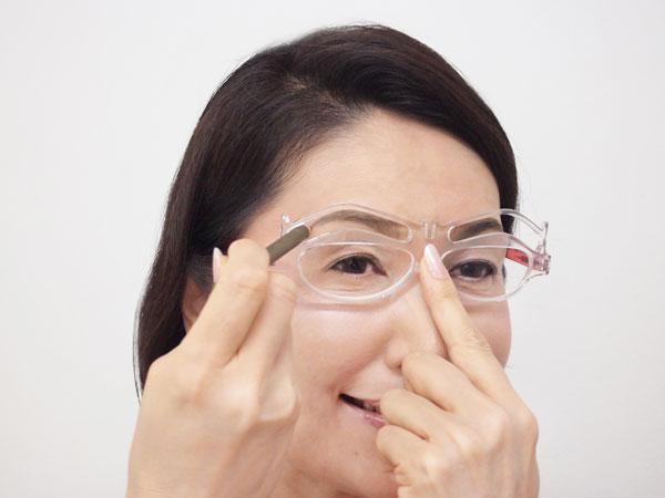 フレームと眉の高さが合う位置を決めたら、メガネの中心を利き手と反対の手で押さえ、アイブロウペンシルを差し込んで眉を描く。 image by REIKO KAZKI 【クリックして拡大】