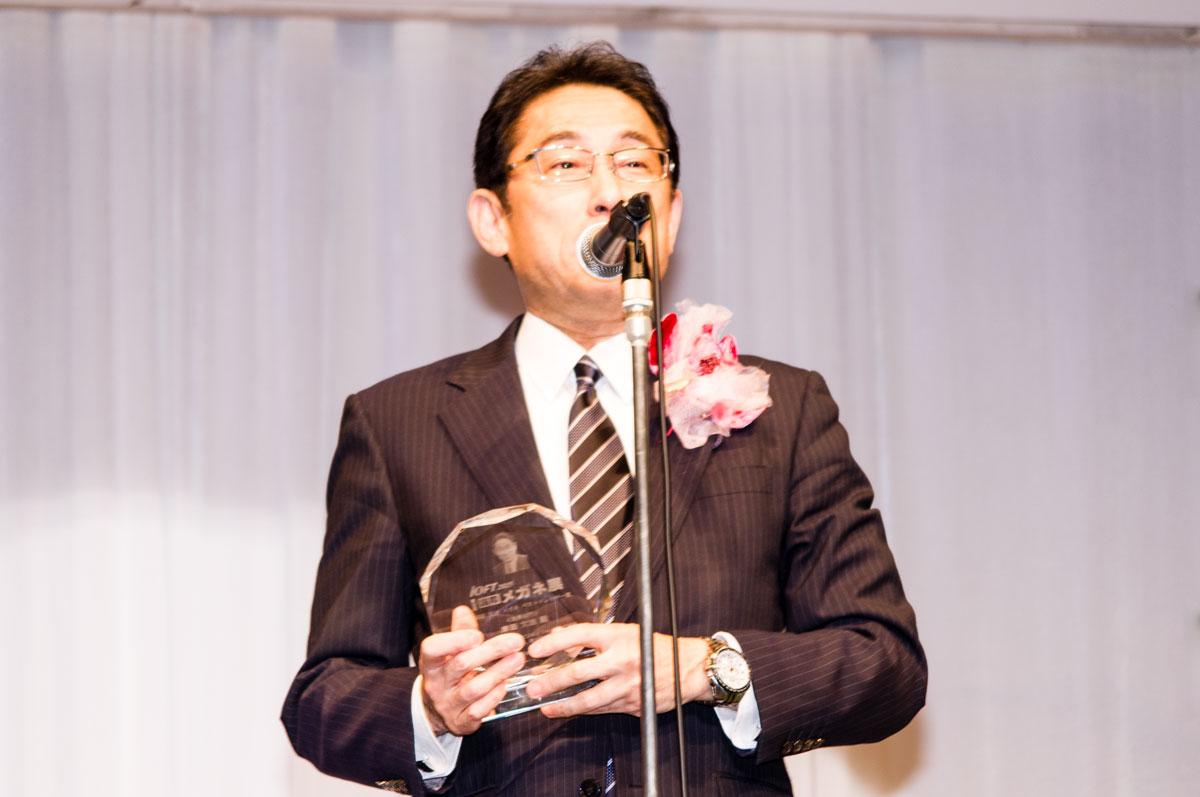 岸田大臣が掛けているメガネは、コルモモード Cor-005 C-1。トロフィーには、岸田大臣の顔が彫り込まれている。