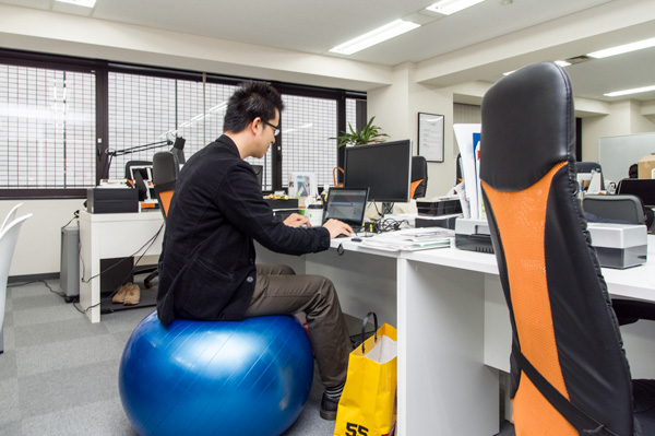 バランスボールに座って仕事するスタッフ。