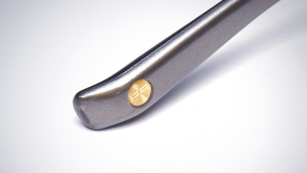 """高い技術力が求められる「3軸ロー付け」や0.1mm単位にこだわったテンプル(つる)のベースとなるのは、""""最高純度""""の品質を追求するアイウェアブランド 999.9(フォーナインズ)のクオリティ。テンプル(つる)先端には、その証として「Fq マーク」が施されている。"""