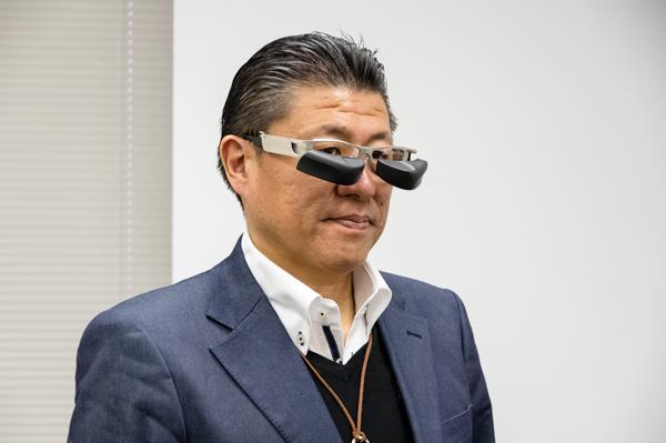 12月15日(木)に都内で開催された発表会では、メガネスーパーの星崎尚彦社長自ら b.g.(ビージー)を装着し披露した。