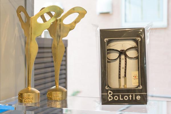 """""""メガネ界のアカデミー賞""""SILMO D'OR(シルモドール)のトロフィー(左)とメガネ型の留め具を使ったループタイ(右)。"""