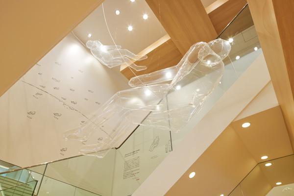 アーティスト鈴木康広氏による展示を期間限定で開催中。2階へつながる吹き抜けには、透明なフィルムで隔たれた人の形をした空気を展示。 image by JINS