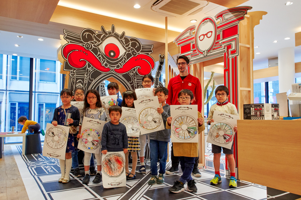 塗り絵を手にした子どもたちはニコラ・ビュフ氏と記念撮影。
