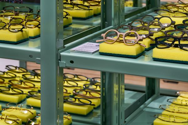 什器には既製のスチールラックを利用し、既製の黄色いキッチンスポンジの上にメガネが置かれている。