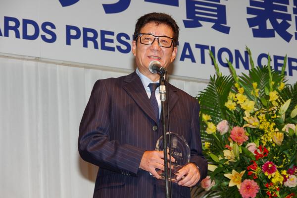 自身のメガネ姿が彫り込まれたトロフィーを手に、受賞の喜びを語る松井一郎氏。