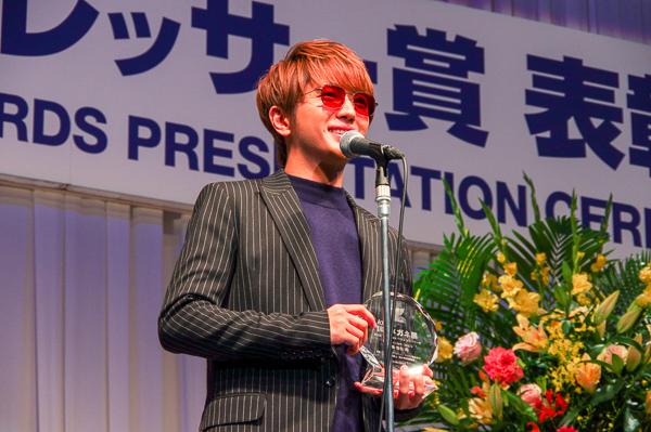 自身のメガネ姿が彫り込まれたトロフィーを手に、受賞の喜びを語る西島隆弘さん。