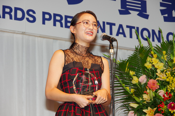 自身のメガネ姿が彫り込まれたトロフィーを手に、受賞の喜びを語る岡田結実さん。