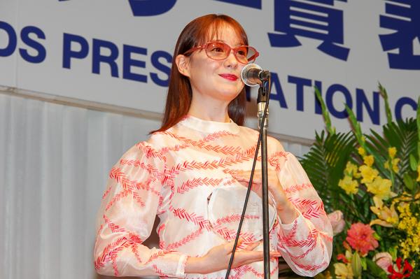 自身のメガネ姿が彫り込まれたトロフィーを手に、受賞の喜びを語るトリンドル玲奈さん。